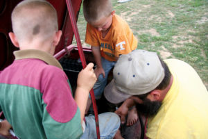 A dad working on his vehicle with two of his little boys looking on