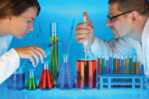 Male and female scientists mixing chemicals in test tubes and bottles in a laboratory