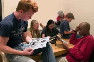 Variety of people from different ethnic groups reading Good and Evil illustrated graphic novel