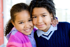African American girl hugging her brother