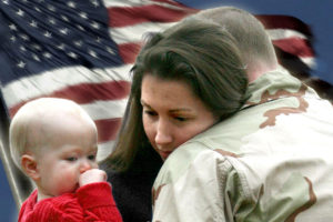 Serviceman hugging his wife and baby while Old Glory waves in the background
