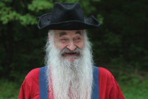 Smiling elderly man with white beard wearing black, red and blue