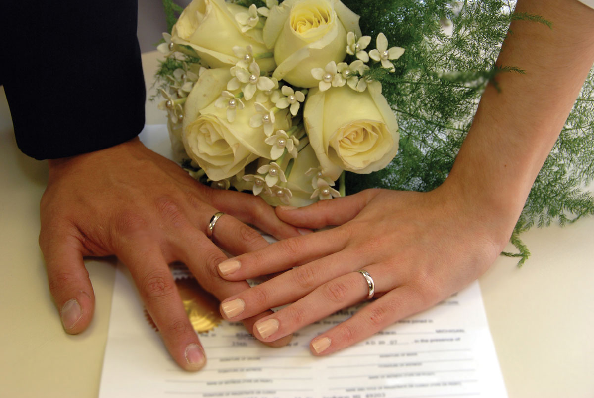 Man and woman's hands lying on top of their marriage contract with yellow roses