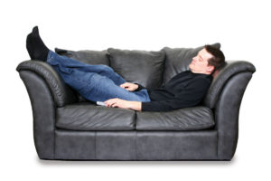 Young husband asleep on leather couch