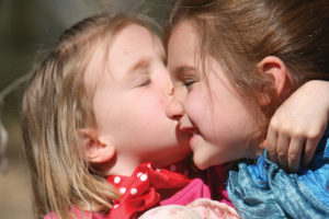 A little blonde haired girl giving her big sister a kiss