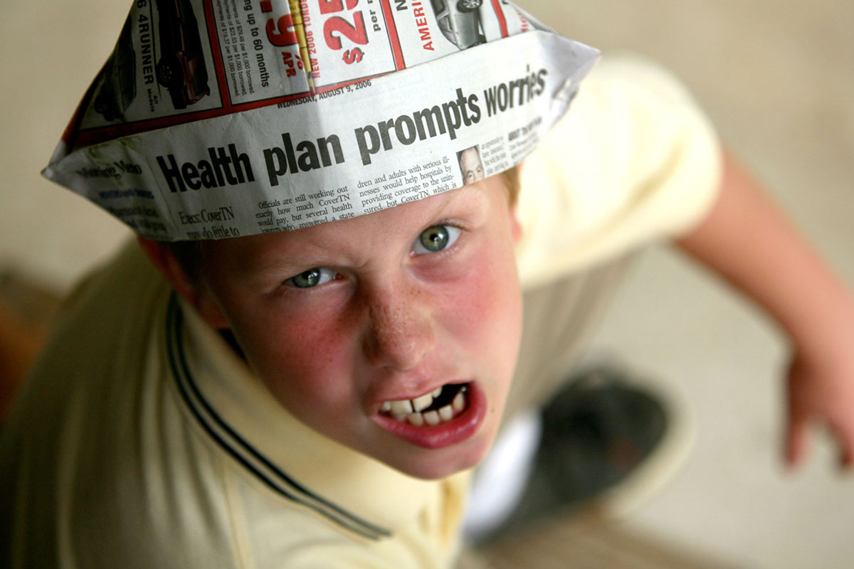 Angry protesting little boy wearing newspaper hat