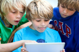 Three young boys interacting with a tablet computer device