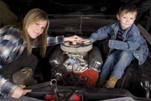 Mom and son working on car maintenance together