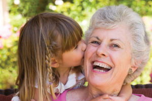 A laughing grandmother being kissed by her blonde haired little granddaughter in pink