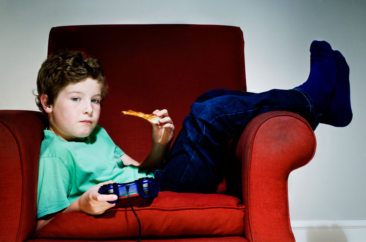 Boy on couch holding video game controller and slice of pizza