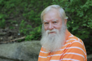 Older man with white beard wearing orange polo shirt