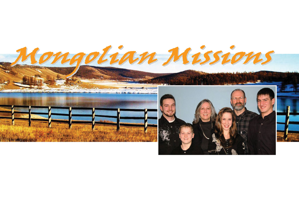 Missionary family picture in front of scenic picture taken in Mongolia