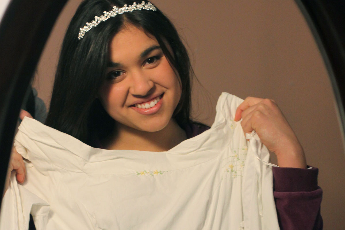 Dark haired dark eyed tan skinned young woman wearing sparkling headband holding up her wedding dress before a mirror preparing to be a help meet