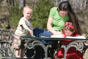 A mom homeschooling her little girl and toddler