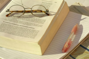 Glasses, books, notebook, and pen.