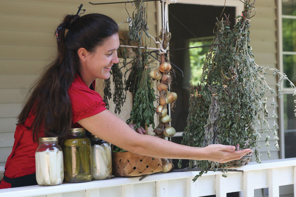 Dark haired young wife growing herbs on her front porch