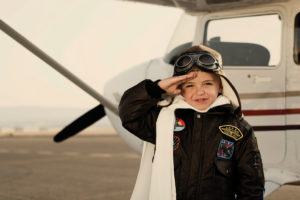 Miniature pilot stands beside plane and salutes