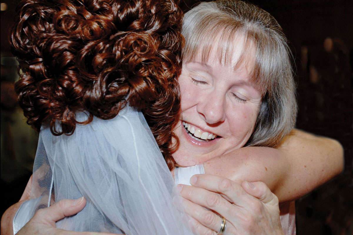 A bride with curly red hair hugs her mother