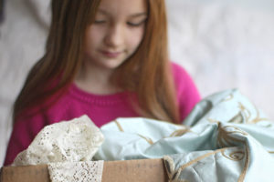 Young girl with a box of fabric