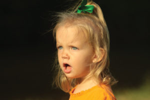 Angry little blonde-haired girl wearing orange and green