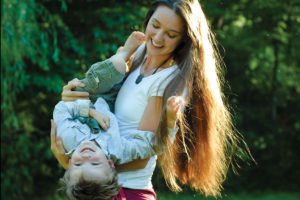 Mother playfully turning her four year old son upside down for a moment