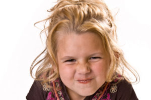 Blonde haired little girl with a cute scrunched up amused look on her face