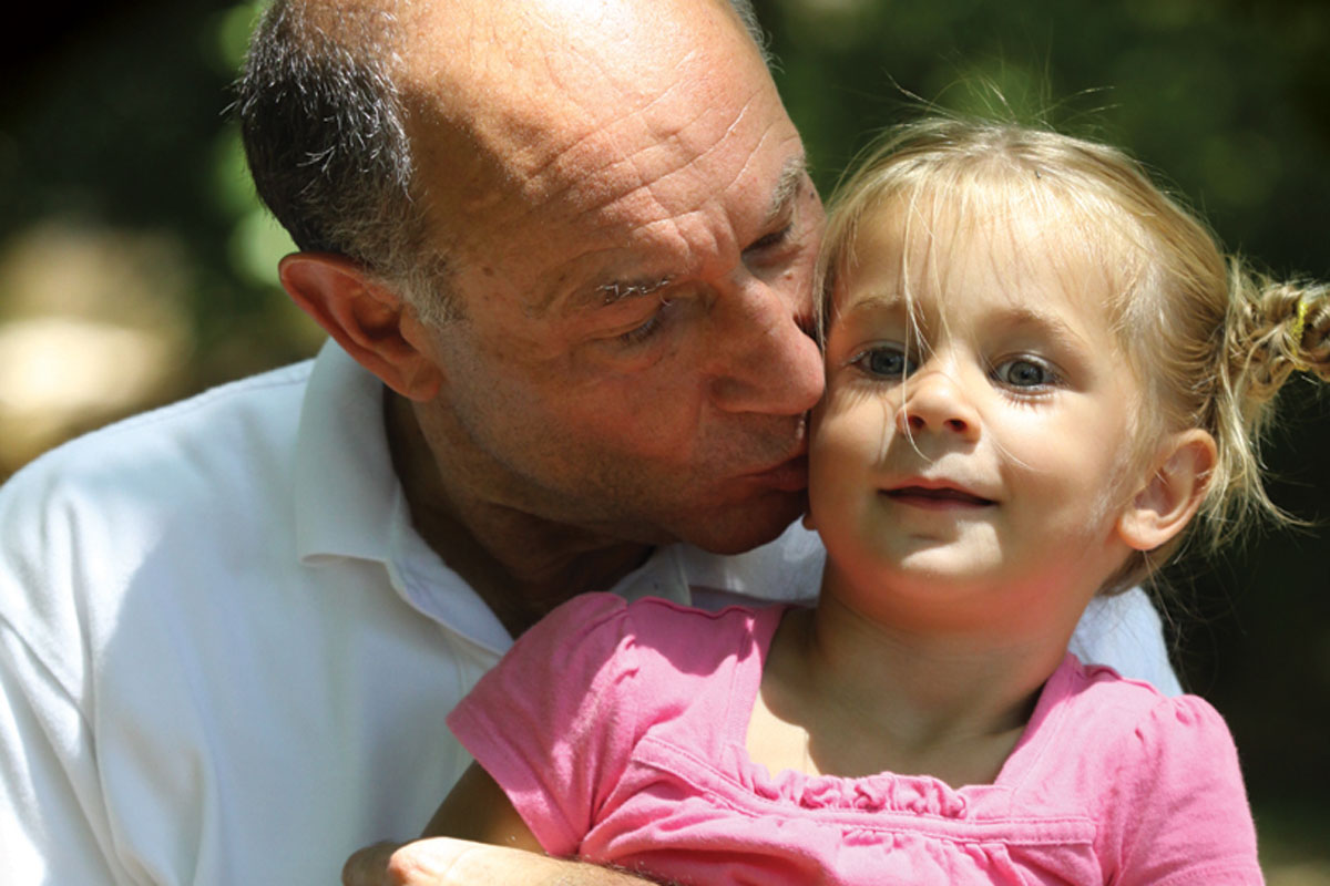 Grandfather planting a kiss on the cheek of his little blonde haired granddaughter
